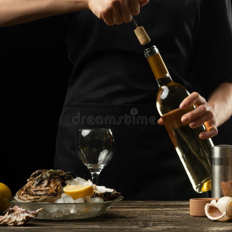 O cozinheiro chefe abre o vinho seco italiano com as ostras com limão, em um fundo escuro imagem de stock