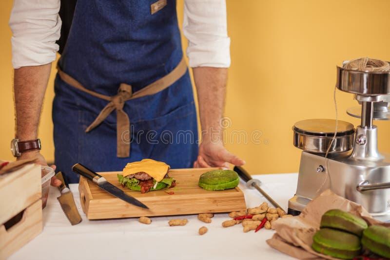 O cozinheiro chefe adiciona a manjericão no hamburguer que cozinha o conceito do Hamburger foto de stock royalty free