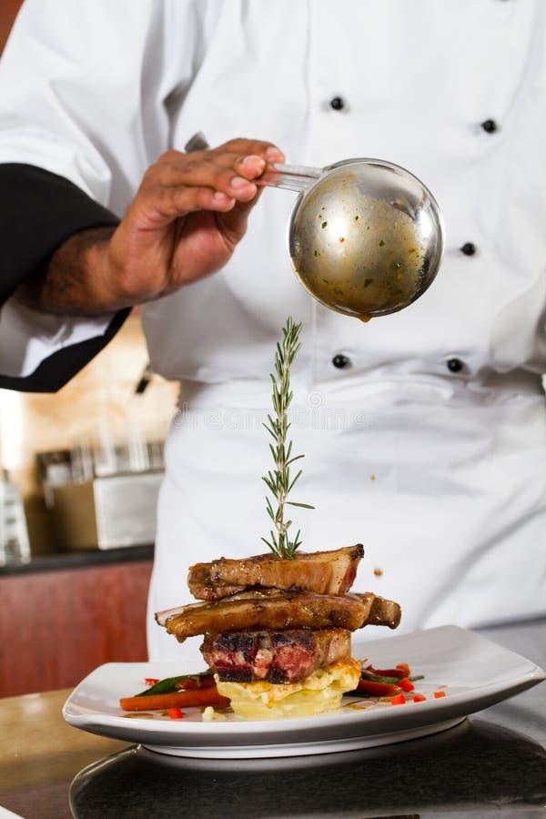O cozinheiro chefe adiciona o molho foto de stock royalty free