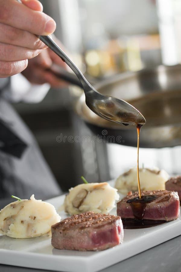 O cozinheiro chefe adiciona o sause aos bifes de uma carne, backgroung cinzento foto de stock