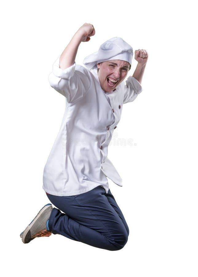 O cozinheiro chefe agradável da jovem mulher está saltando Sente realmente feliz imagem de stock