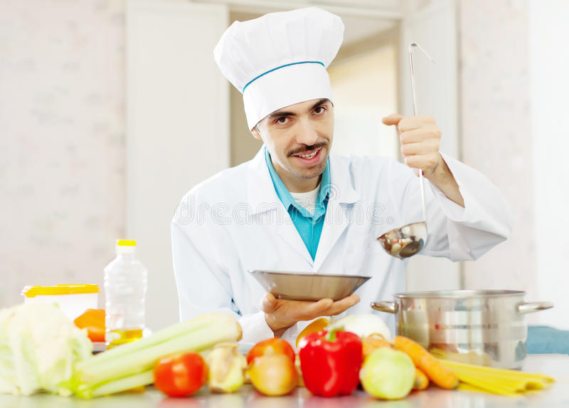 O cozinheiro chefe caucasiano com concha derrama a sopa imagens de stock royalty free