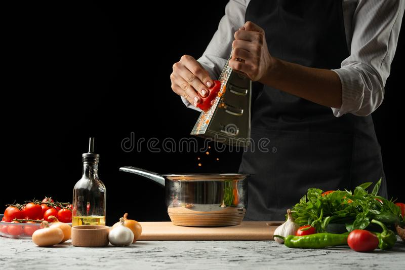 O cozinheiro chefe corta e prova os tomates, preparando um molho de tomate italiano para o macarrão Pizza O conceito da receita d fotos de stock royalty free
