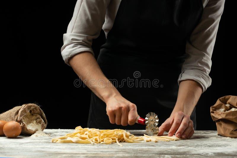 O cozinheiro chefe corta a massa italiana da massa Close up Um conceito para preparar o alimento delicioso, a culinária italiana  fotos de stock royalty free
