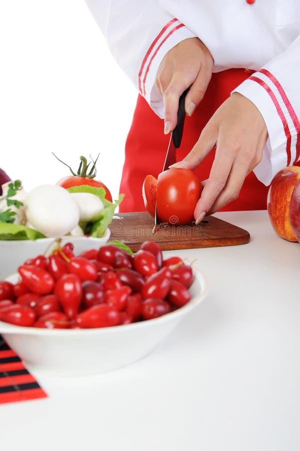 O cozinheiro chefe corta o tomate imagens de stock