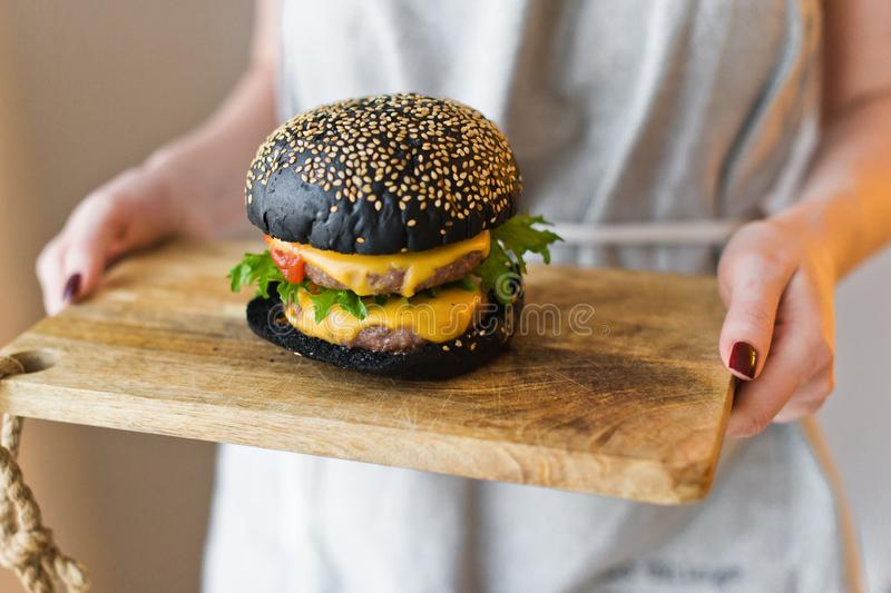 O cozinheiro chefe da menina realiza em suas m?os uma placa de corte de madeira com cheesburgers pretos imagem de stock