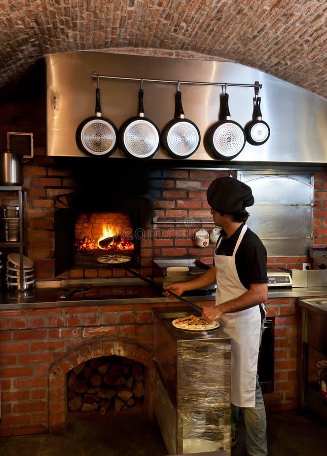 O cozinheiro chefe da pizza põr a pizza dentro do forno de madeira foto de stock