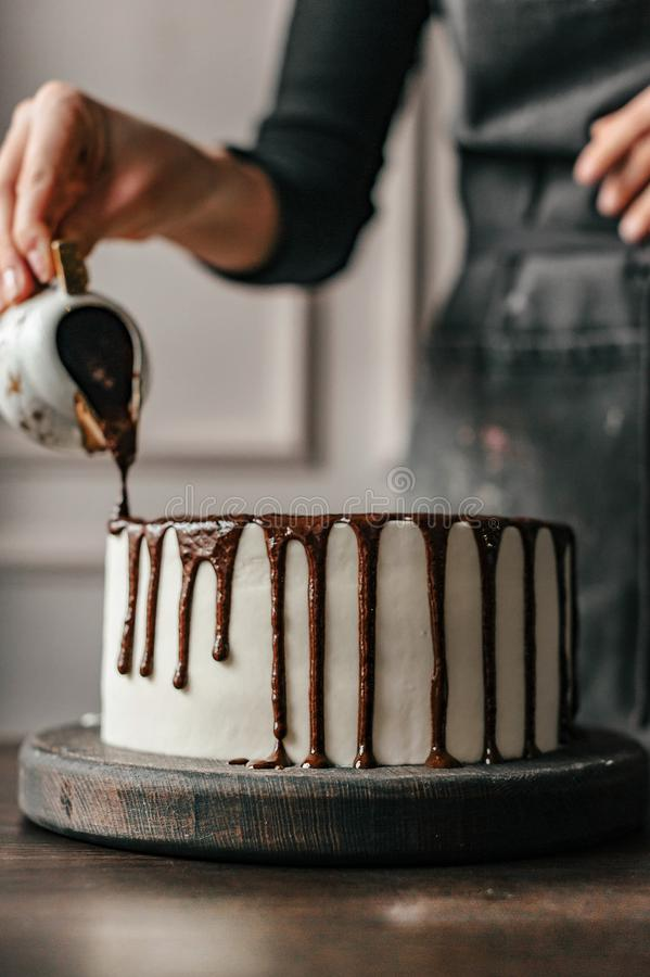 O cozinheiro chefe de pastelaria decora um bolo de chocolate Close-up imagem de stock royalty free