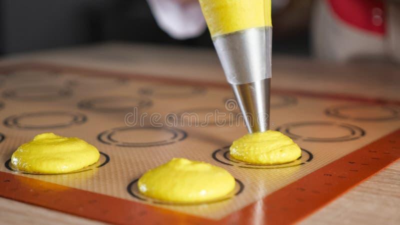 O cozinheiro chefe de pastelaria est? cozinhando bolinhos de am?ndoa Massa de derramamento na esteira do silicone do est?ncil fotos de stock royalty free