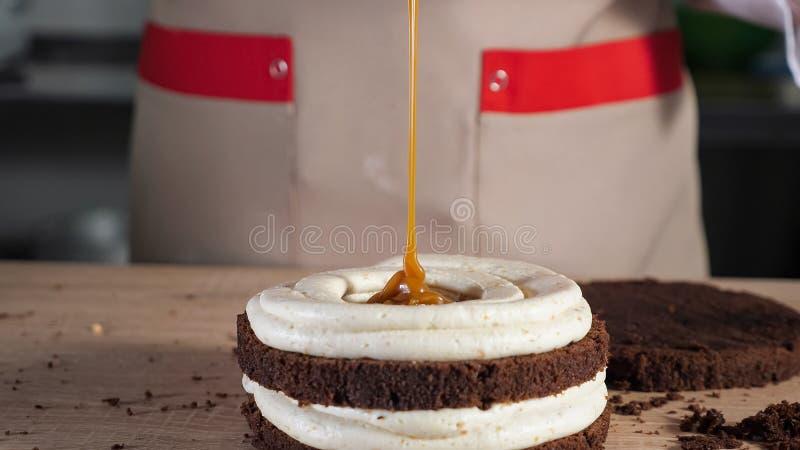 O cozinheiro chefe de pastelaria est? derramando o caramelo no bolo de esponja do chocolate Fazendo o bolo na padaria foto de stock royalty free