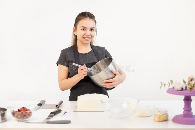 O cozinheiro chefe de pastelaria moreno atrativo da menina no avental chicoteia o bolo de creme em uma bacia do metal imagens de stock
