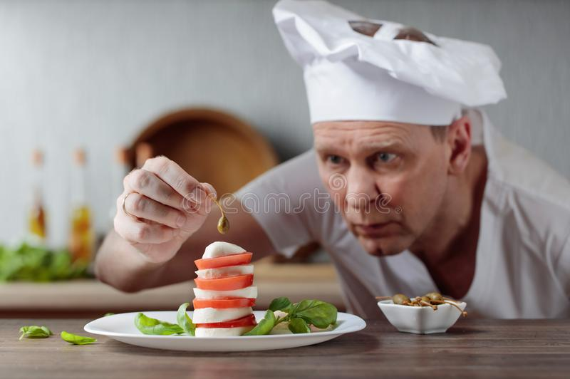 O cozinheiro chefe decora petiscos com mussarela e alcaparras imagens de stock royalty free