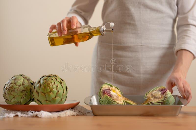 O cozinheiro chefe derrama o azeite e prepara-se para cozer a alcachofra em um fundo claro, o conceito de cozinhar o alimento sab fotografia de stock royalty free