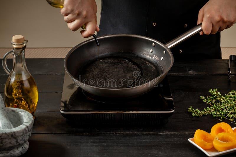 O cozinheiro chefe derrama o azeite em uma bandeja para fazer o prato novo imagem de stock royalty free