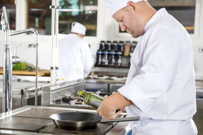 O cozinheiro chefe derrama o azeite na bandeja em uma cozinha profissional foto de stock royalty free