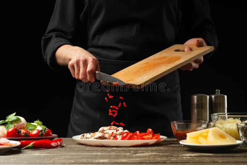 O cozinheiro chefe derrama pimentas quentes em uma placa Para cozinhar burritos, pizza, alface Um conceito delicioso e picante do foto de stock