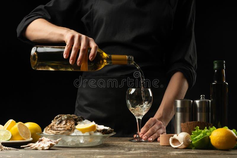 O cozinheiro chefe derrama, prova o vinho seco italiano da ostra com limão imagem de stock