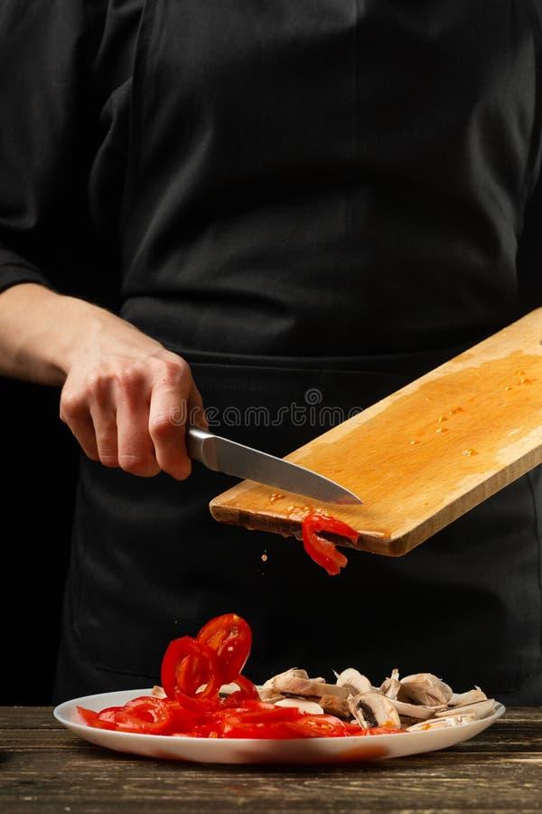 O cozinheiro chefe derrama tomates de cereja em uma placa Frost no movimento Para preparar a pizza, molho de tomate, salada Conce fotografia de stock royalty free