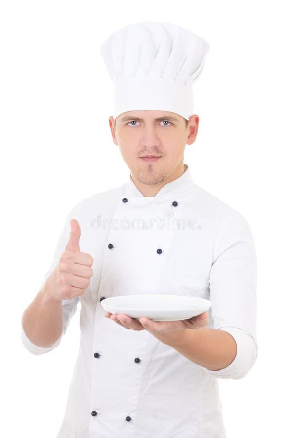 O cozinheiro chefe do homem novo nos polegares uniformes levanta e mostrando o iso vazio da placa imagem de stock
