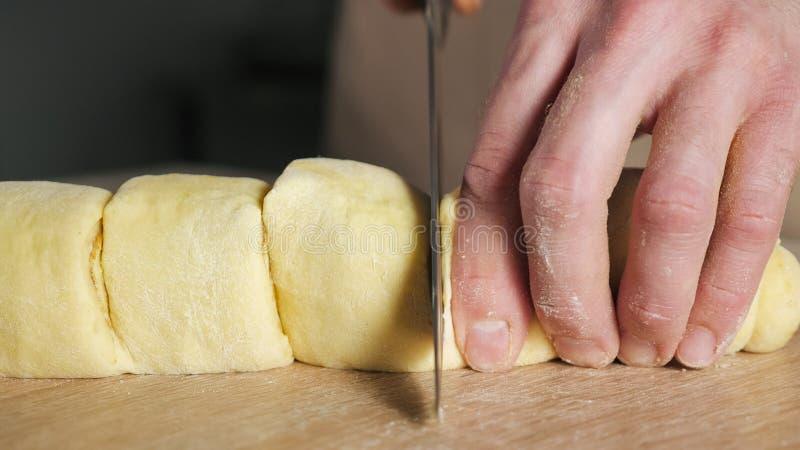 O cozinheiro chefe do padeiro corta o rolo com canela, a??car e manteiga em parcelas para cozer rolos de canela foto de stock