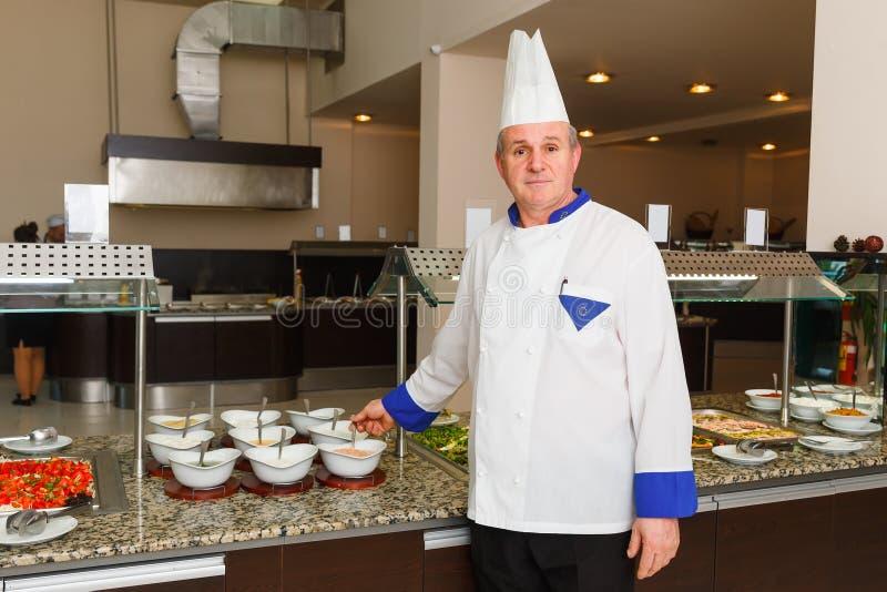 O cozinheiro chefe do restaurante da maravilha do hotel levanta no local de trabalho imagem de stock royalty free