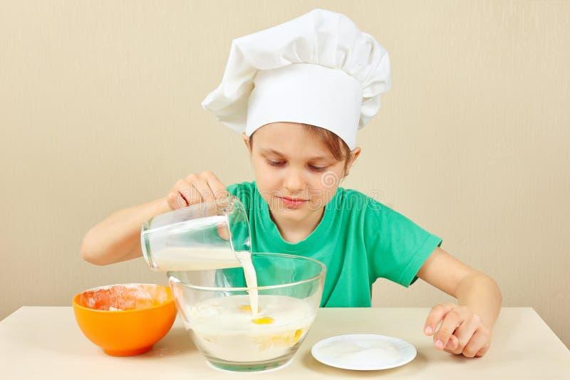 O cozinheiro chefe engraçado pequeno derrama o leite para o bolo de cozimento imagem de stock royalty free