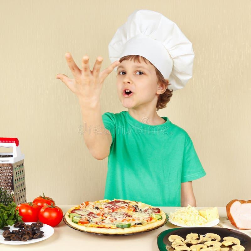 O cozinheiro chefe engraçado pequeno expressivo aprecia a pizza cozinhada imagens de stock