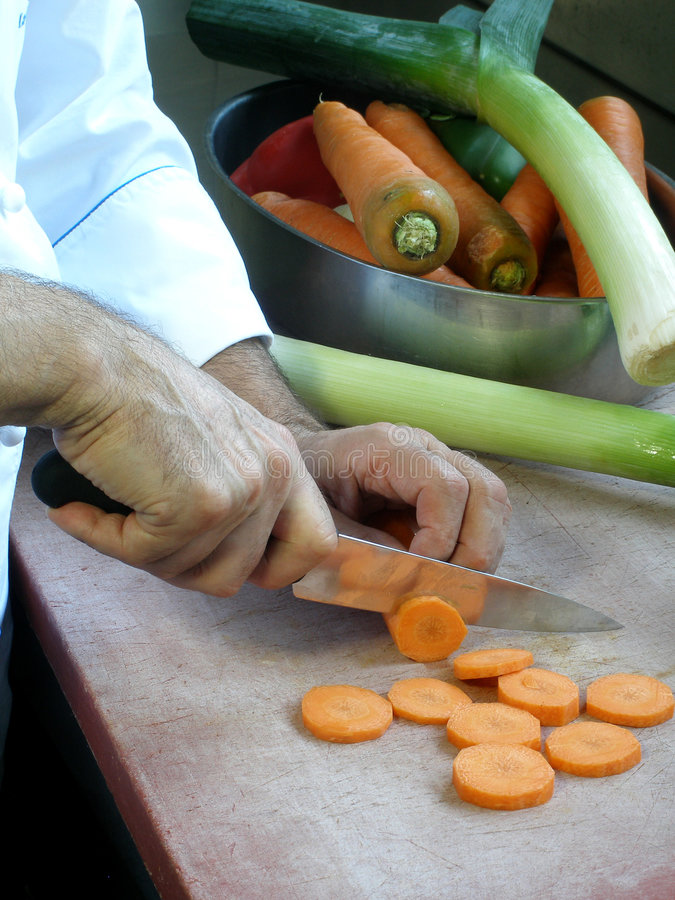 O cozinheiro chefe está cortando cenouras foto de stock royalty free
