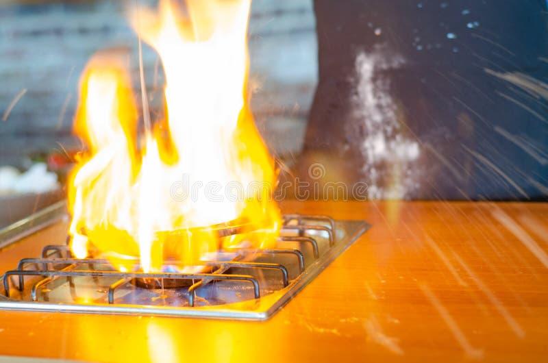 O cozinheiro chefe está cozinhando ovos em um fogão de gás O fogo está saltando ao redor imagens de stock