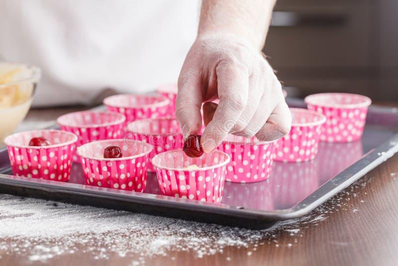 O cozinheiro chefe está decorando queques orgânicos deliciosos bolos do copo da cereja mim foto de stock royalty free