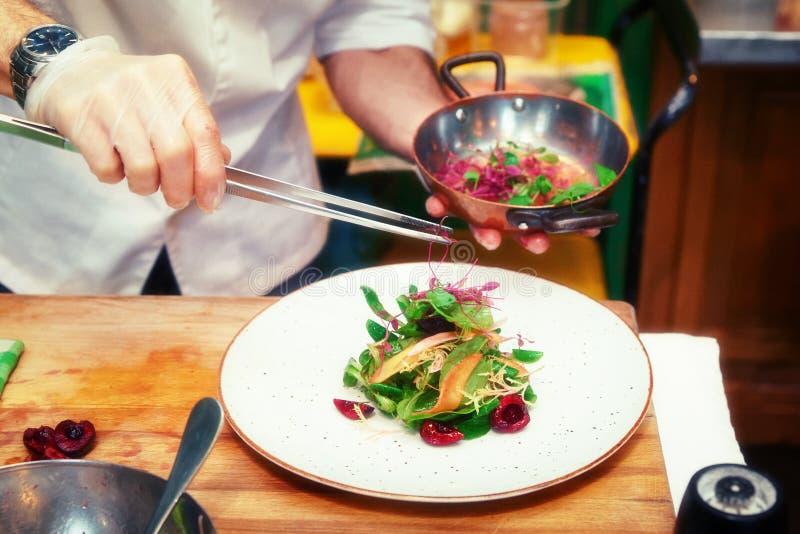 O cozinheiro chefe está fazendo o aperitivo vegetal, tonificado fotos de stock