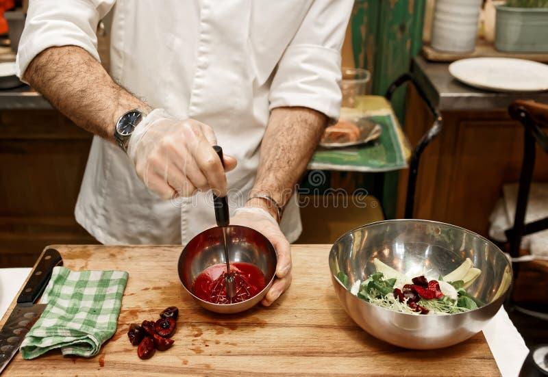 O cozinheiro chefe está fazendo o molho da salada, tonificado foto de stock