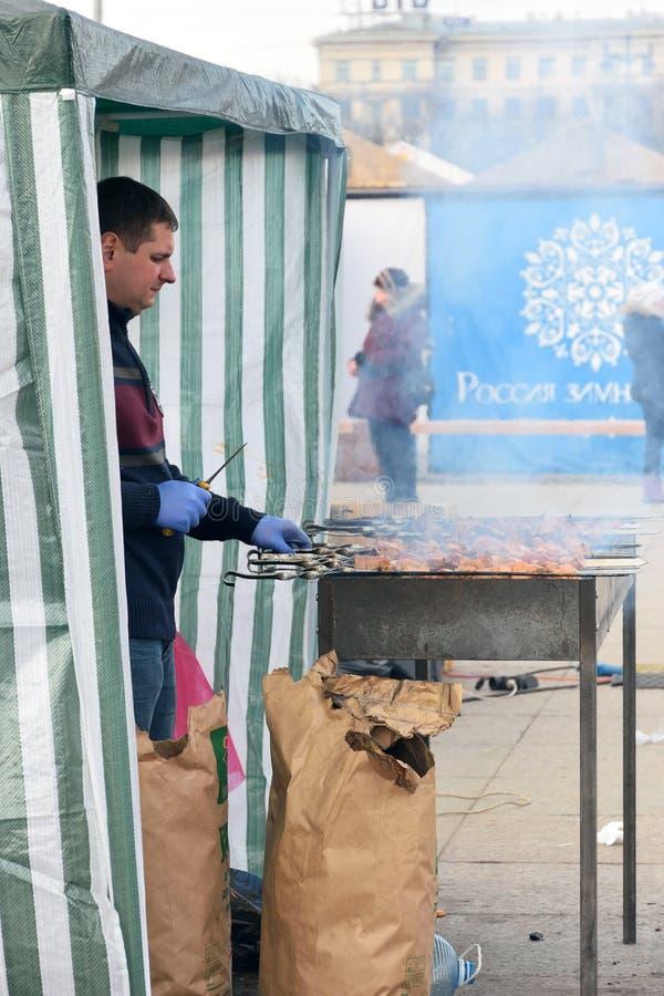 O cozinheiro chefe está grelhando no espeto na grade na rua sobre fotografia de stock royalty free