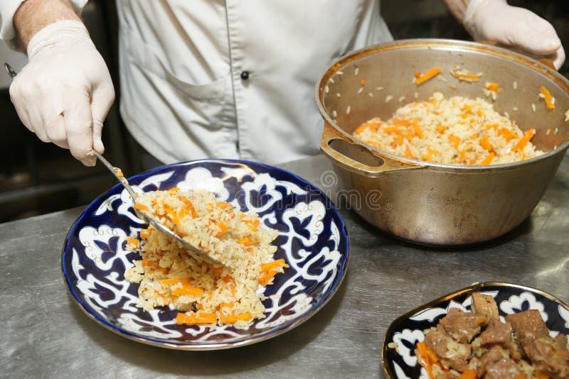 O cozinheiro chefe está servindo o pilau na cozinha do restaurante imagens de stock royalty free