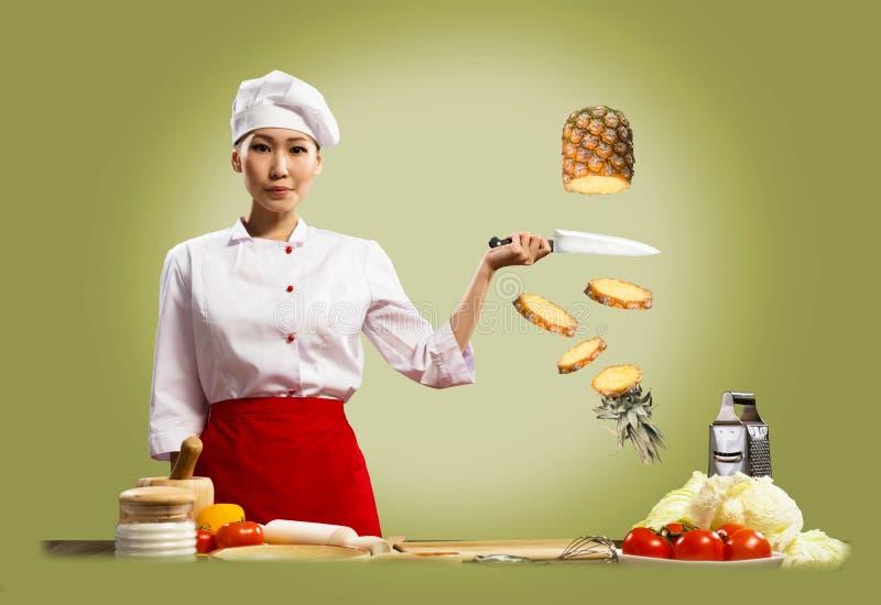 O cozinheiro chefe fêmea asiático corta o abacaxi imagem de stock