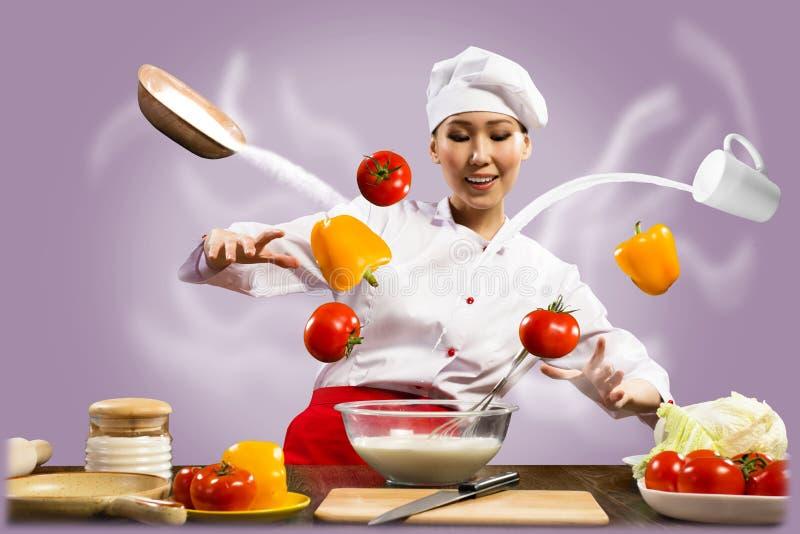 O cozinheiro chefe fêmea asiático na cozinha conjura imagens de stock