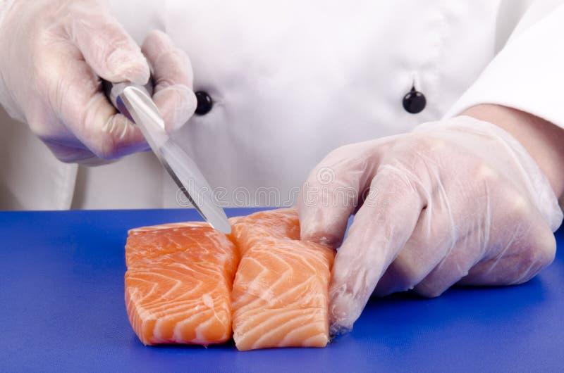 O cozinheiro chefe fêmea corta as faixas salmon foto de stock