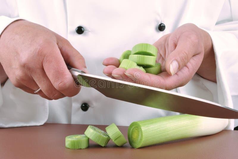 O cozinheiro chefe fêmea corta o alho-porro imagens de stock royalty free