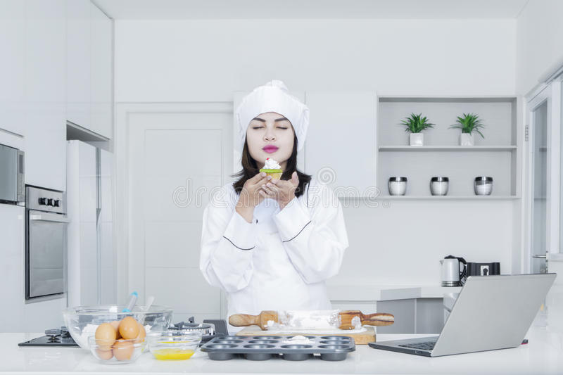 O cozinheiro chefe fêmea guarda um queque na cozinha fotografia de stock