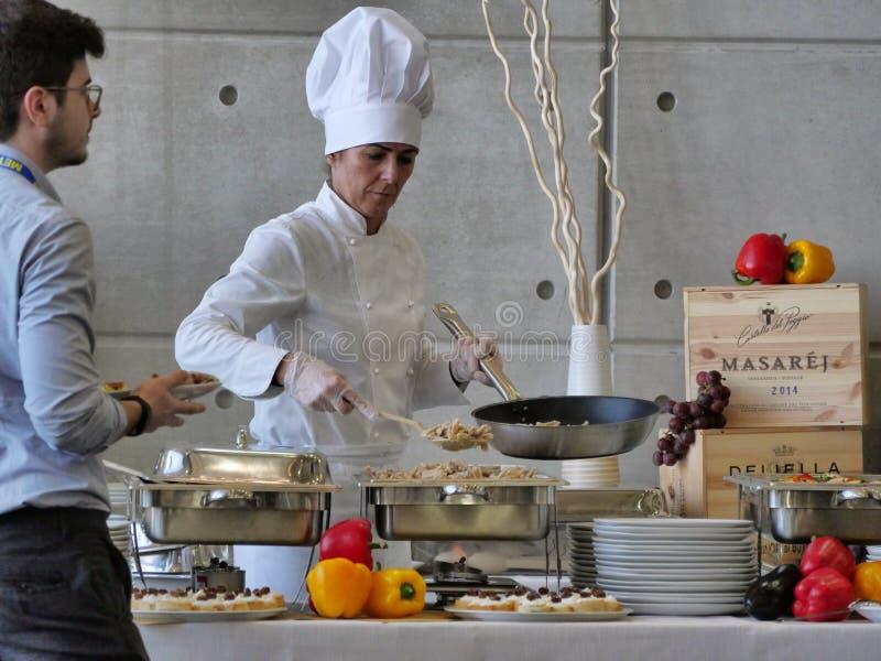 O cozinheiro chefe f?mea profissional prepara o alimento do bufete para clientes imagem de stock