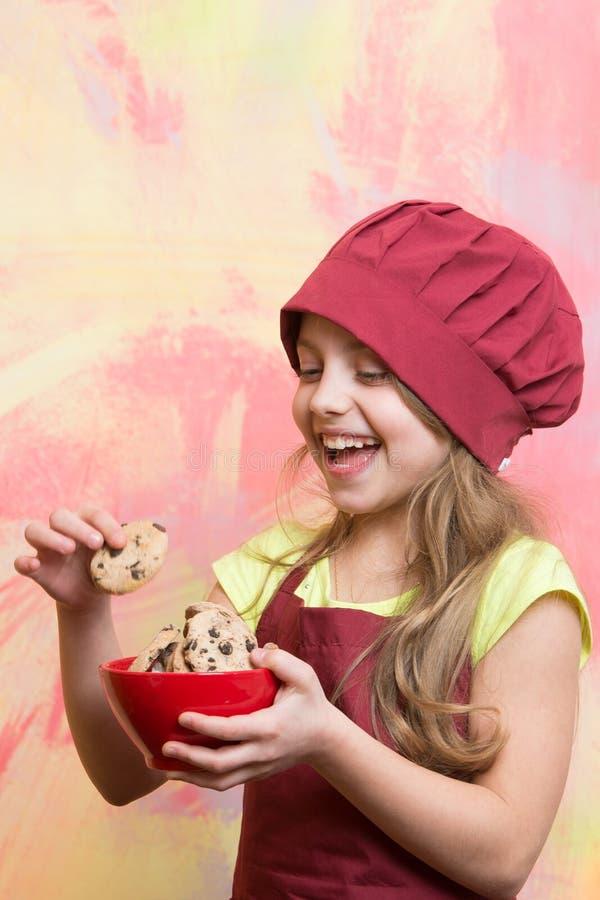 O cozinheiro chefe feliz pequeno da menina no chapéu, avental com cookies rola fotografia de stock royalty free