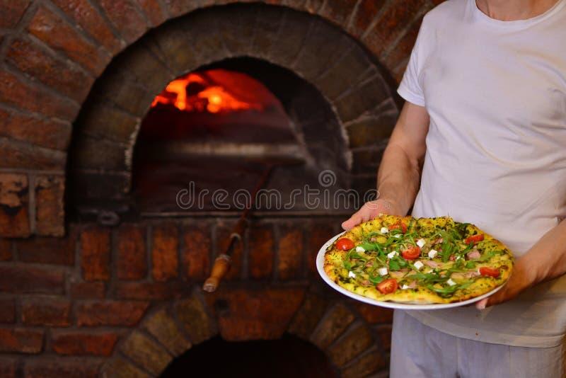 O cozinheiro chefe guarda uma pizza saboroso em suas mãos imagens de stock royalty free