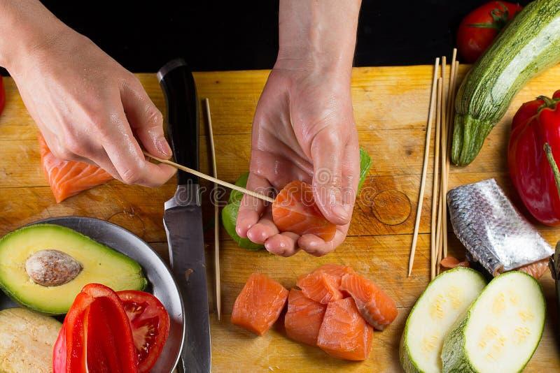 O cozinheiro chefe implating o filett salmon em um espeto fotos de stock royalty free
