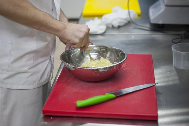 O cozinheiro chefe mói as mãos do ` s do cozinheiro chefe das batatas, placa de desbastamento, ralador fotos de stock royalty free