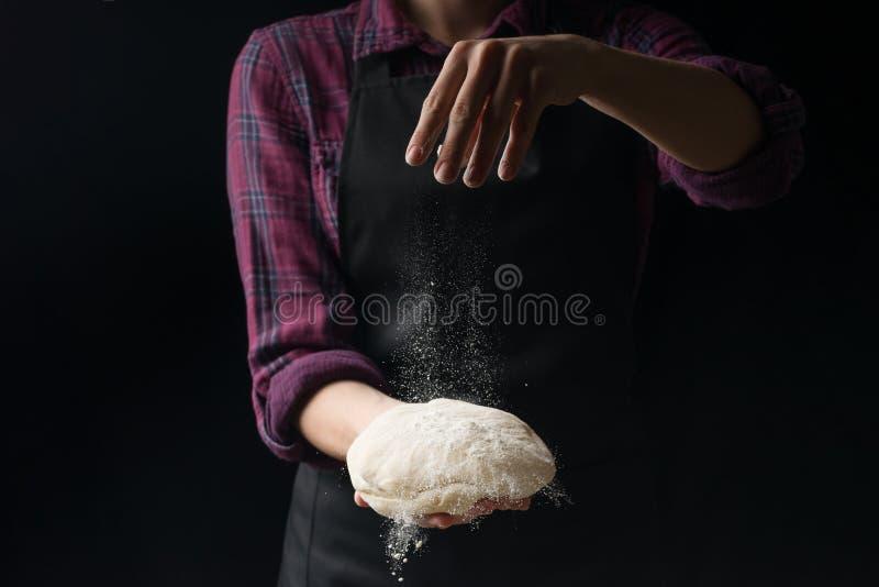 O cozinheiro chefe mantém a massa e derrama a farinha em um fundo escuro O conceito da nutrição fotografia de stock royalty free