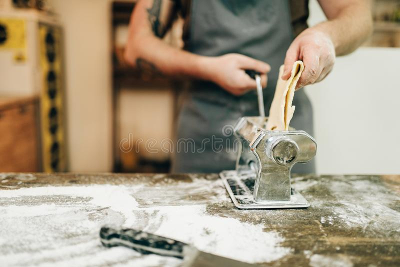 O cozinheiro chefe masculino no avental trabalha com máquina da massa fotografia de stock royalty free