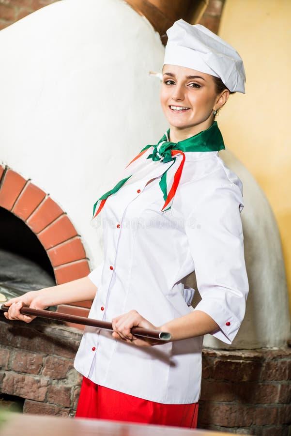 O cozinheiro chefe pôr a massa no forno para pizzas, imagem de stock
