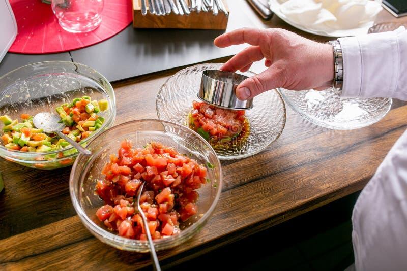 O cozinheiro chefe põe o atum tartare sobre uma placa Classe mestra na cozinha O processo de cozimento Ponto por ponto tutorial C imagens de stock