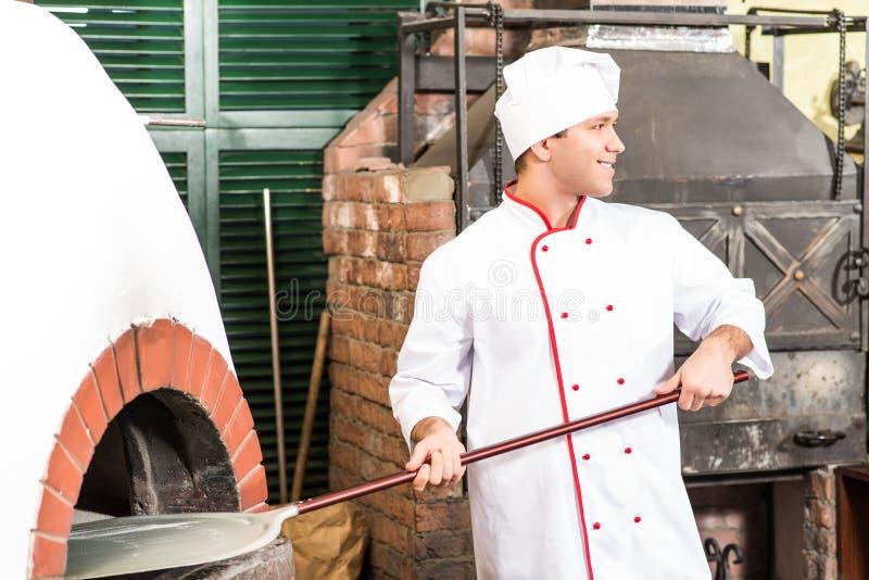 O cozinheiro chefe põr a massa de pão no forno para pizzas, fotografia de stock