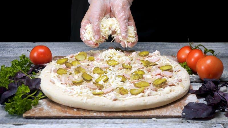 O cozinheiro chefe polvilha a pizza com o queijo raspado Quadro O cozinheiro chefe profissional da pizaria nas luvas p?e a ?ltima imagens de stock royalty free